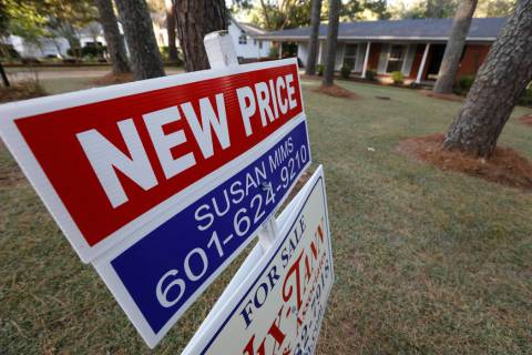 A Sept. 25, 2019, photo shows a sign indicating a new selling price for a house sits atop a Rea ...