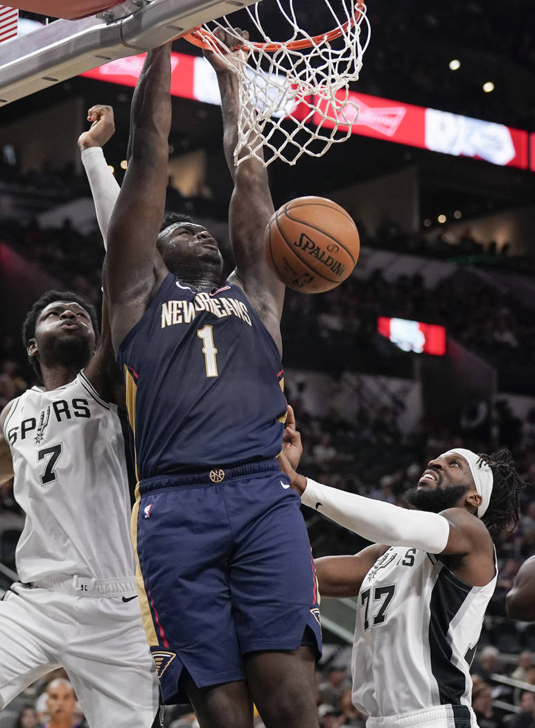 New Orleans Pelicans' Zion Williamson (1) dunks as he is defended by San Antonio Spurs' Chimezi ...