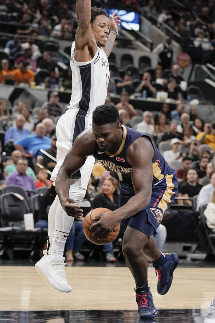 New Orleans Pelicans' Zion Williamson, right, falls as he tangles with San Antonio Spurs' DeMar ...