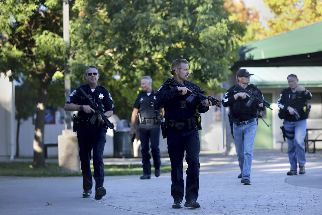 Santa Rosa police officers carry guns as they search the campus of Ridgway High School for susp ...