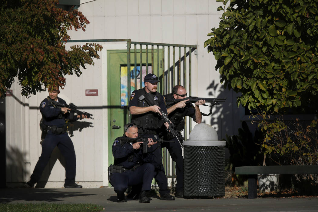 Santa Rosa police officers hold guns as they search the campus of Ridgway High School for suspe ...