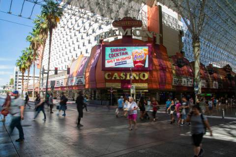People walk by Fremont, owned by Boyd Gaming Corp., in Las Vegas, Wednesday, June 12, 2019. (Mi ...