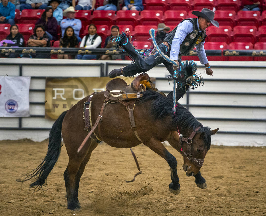 Saddle bronc rider Jay Joaquin gets thrown up into the air above the horse during the first rou ...