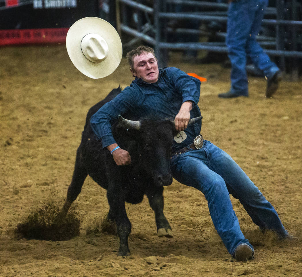 Steer wrestler Tyler Byrne loses his hat but holds onto the steer during the first round of the ...