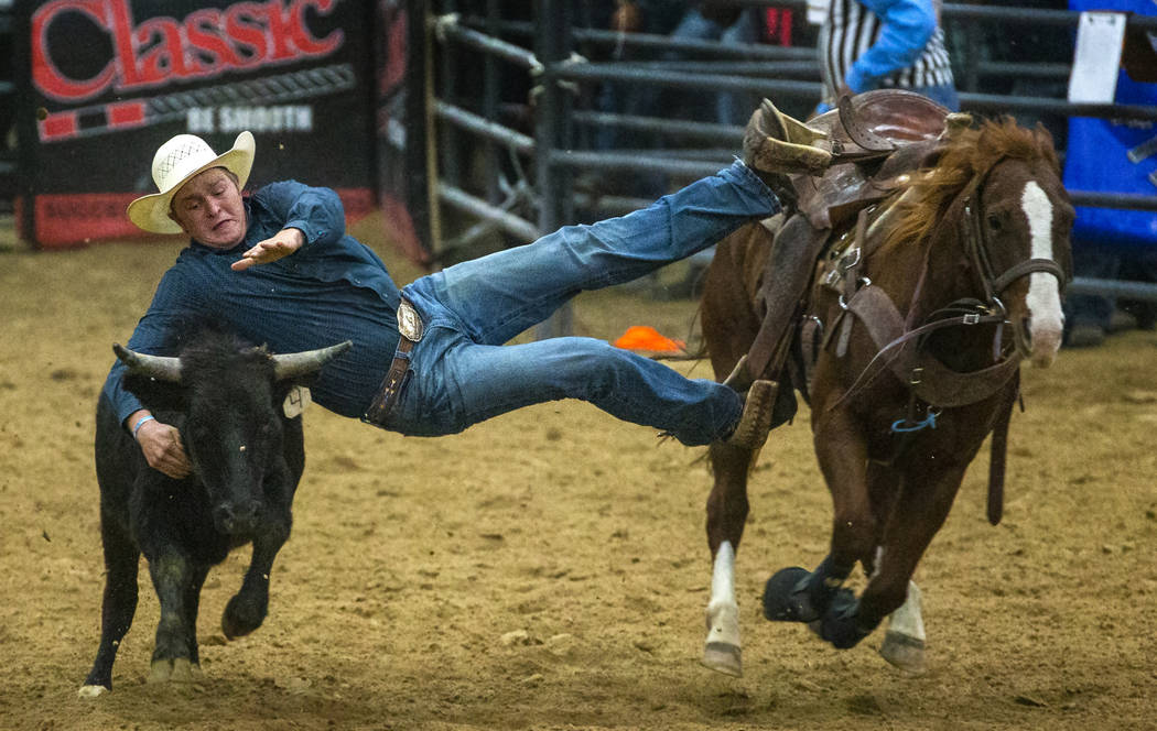 Steer wrestler Tyler Byrne leans way over to grab the steer during the first round of the India ...
