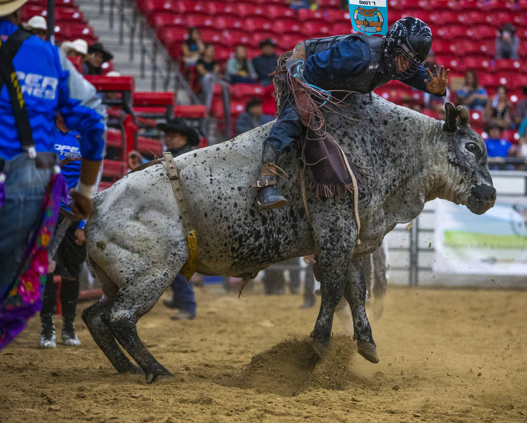 Bull rider Latrell Long is pushed forward but continues to hang onto his bull during the first ...