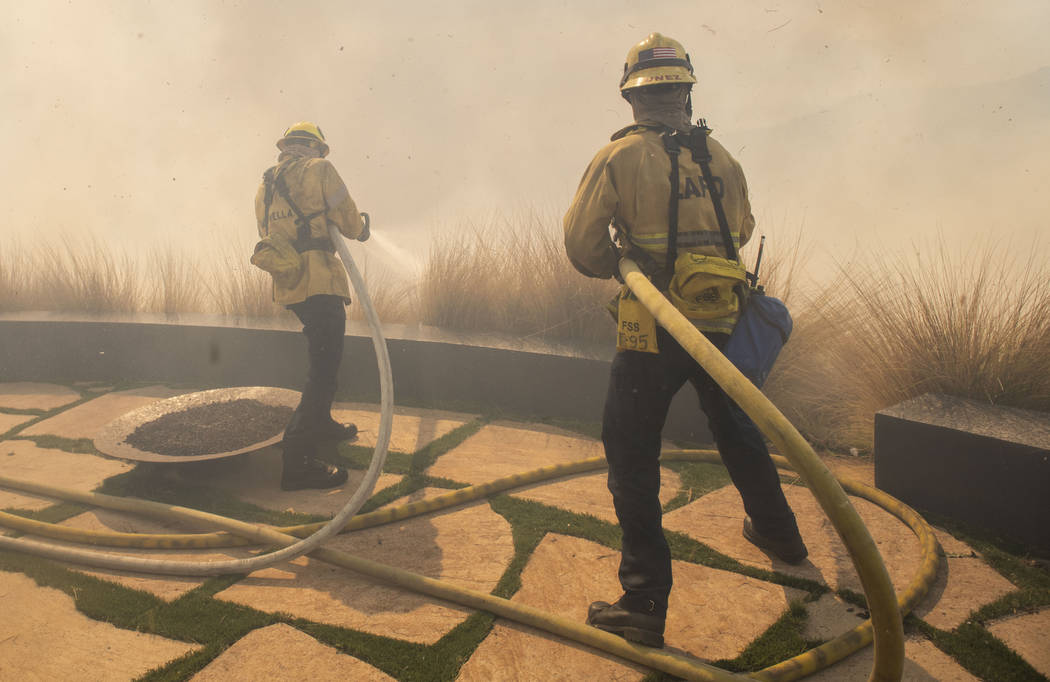 Firefighters protect a home from a wildfire in the Pacific Palisades area of Los Angeles, Monda ...