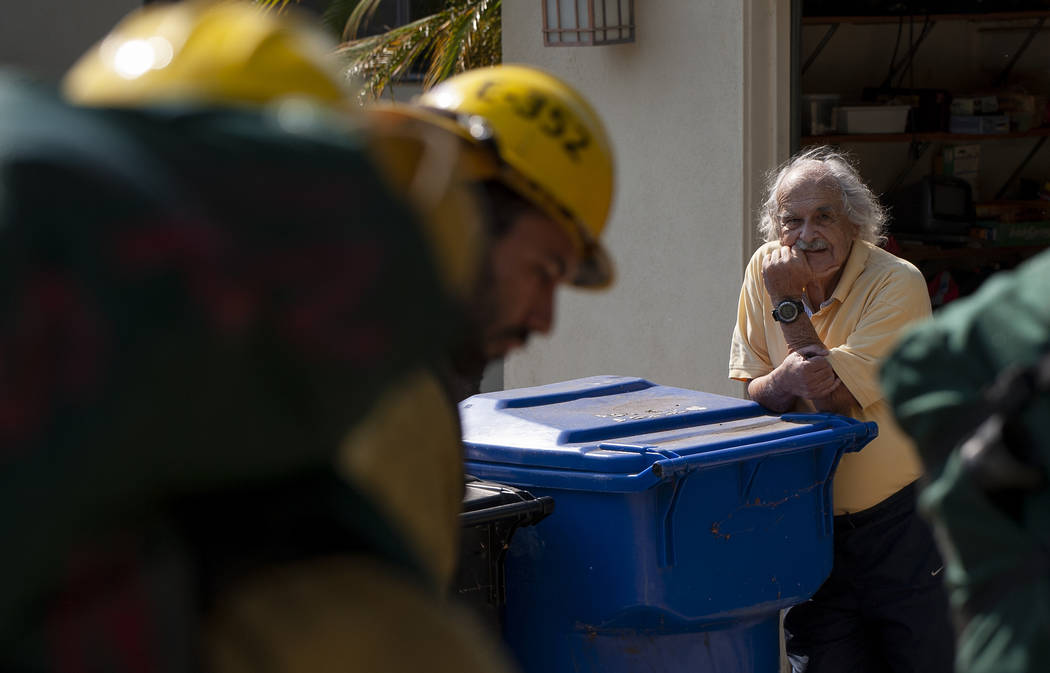 A man watches as firefighters prepare to enter his backyard to fight a wildfire in the Pacific ...