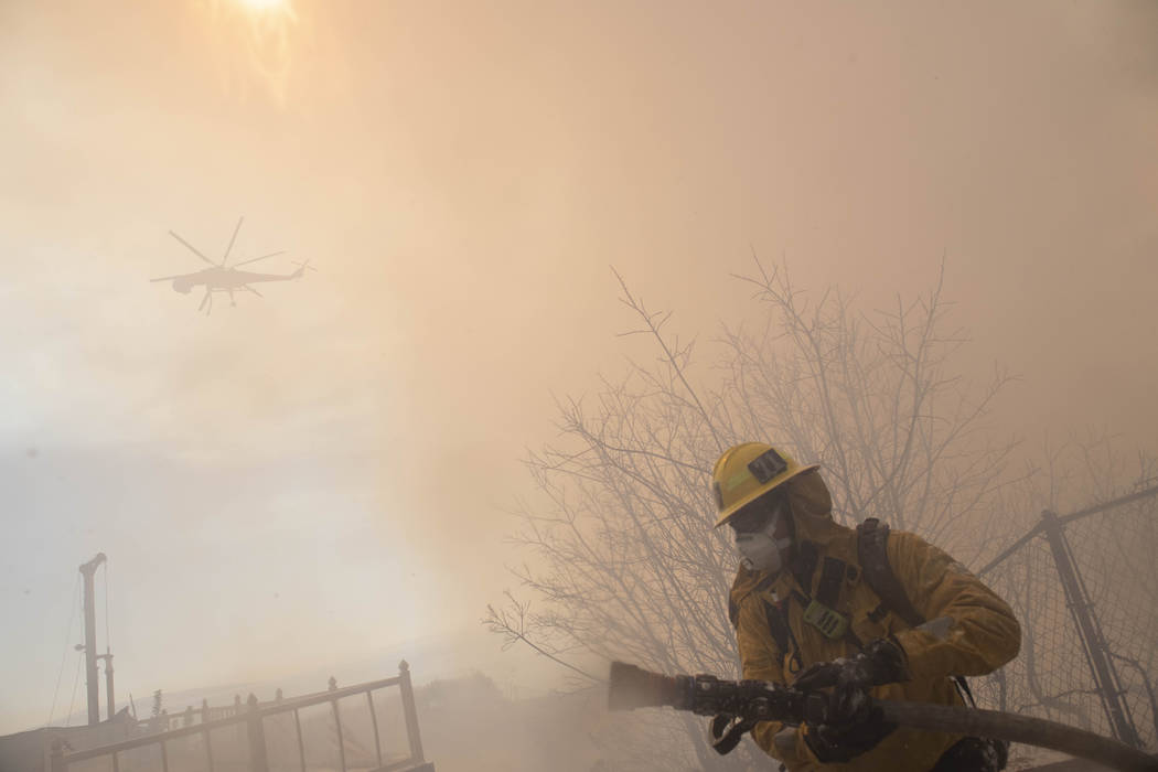 A firefighter carries a hose during work to protect homes from the flames of a wildfire in the ...