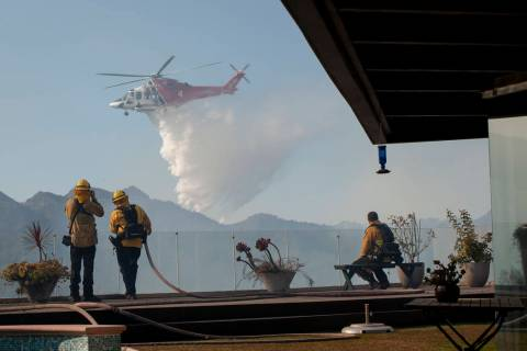 Firefighters watch as a helicopter drops water in a wildfire in the Pacific Palisades area of L ...