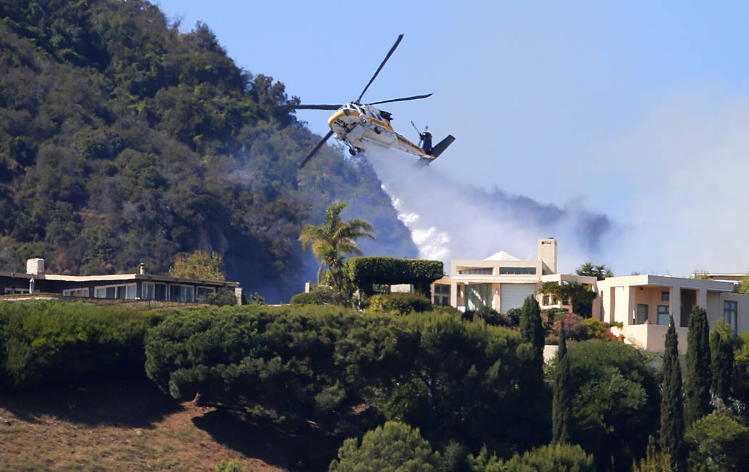 A Los Angeles County Fire Department helicopter makes a water drop as flames from a wildfire th ...