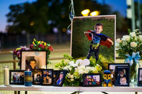 Photos of Gavin Murray Palmer, who died in a house fire, during a candlelight vigil in his memo ...