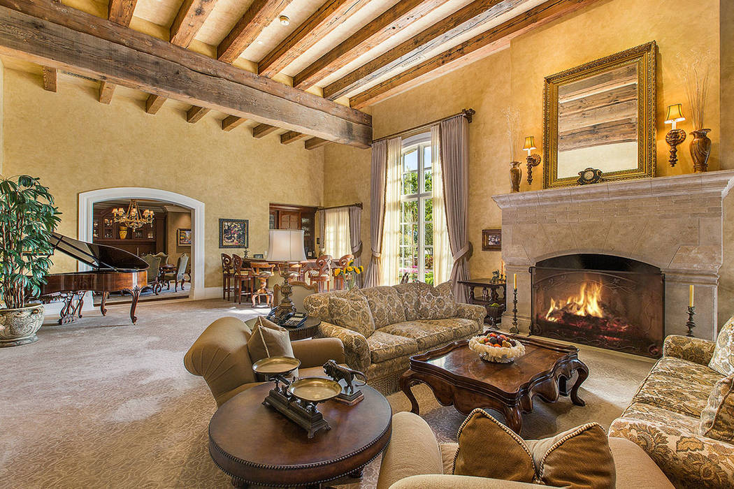 Fraser Almeida /Luxury Home Photography The living room has a traditional fireplace.