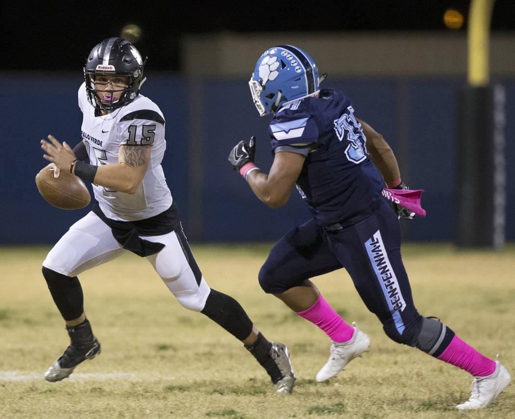 Palo Verde senior quarterback Paul Myro (15) scrambles away from Centennial senior Leonard Robb ...