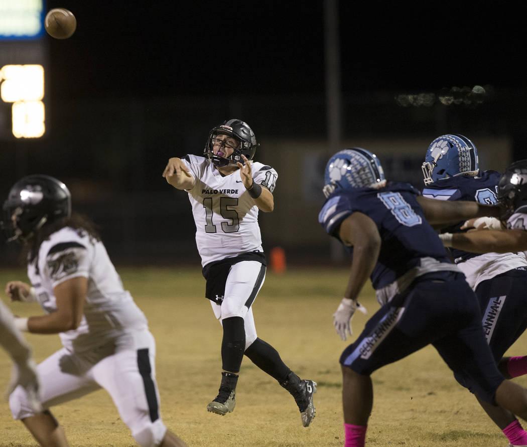 Palo Verde senior quarterback Paul Myro (15) makes a running throw over Centennial senior Thoma ...