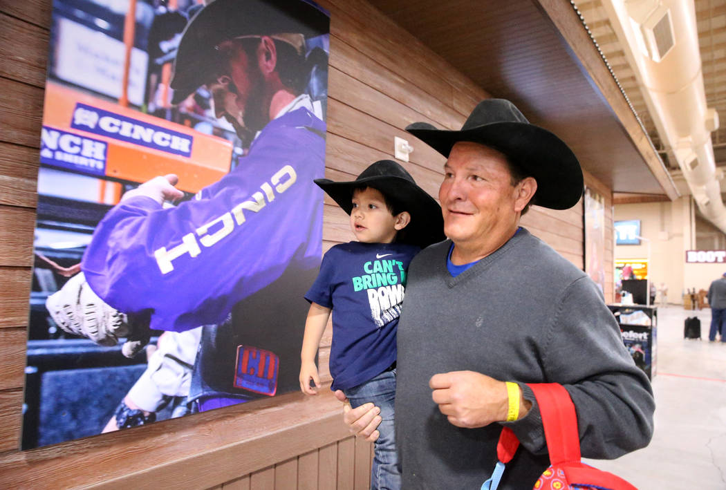 Mike Not Afraid and his grandson, Grayson Spotted Bear, 2, walk to the arena during Indian Nati ...