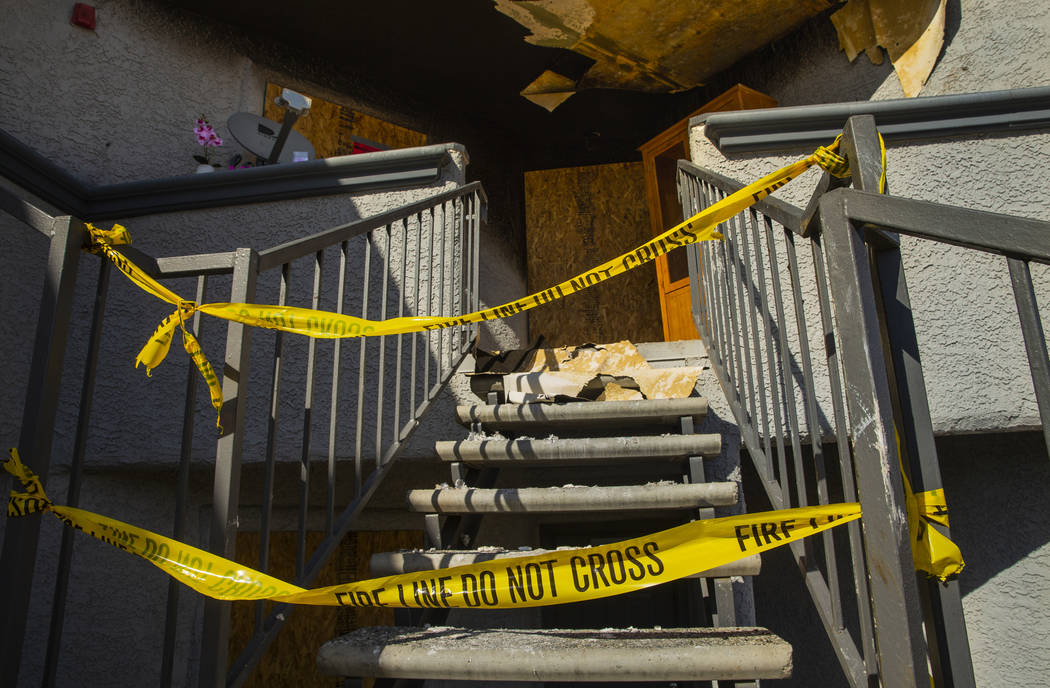 Fire department warning tape blocks the upstairs entrance from an early morning fire at The Bri ...