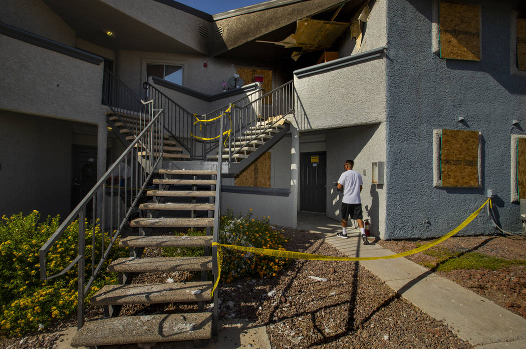 A maintenance worker heads inside a lower apartment where an early morning fire occurred at The ...
