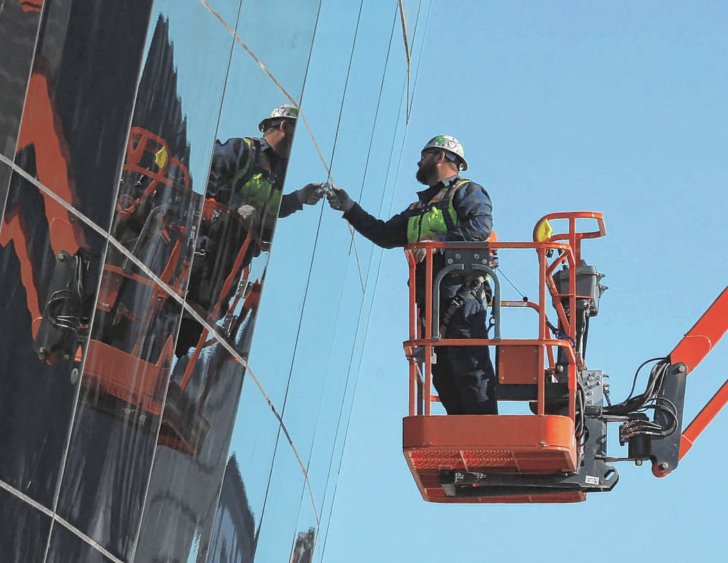 Workers check installed glass on the east side of the Raiders Allegiant Stadium in Las Vegas, T ...