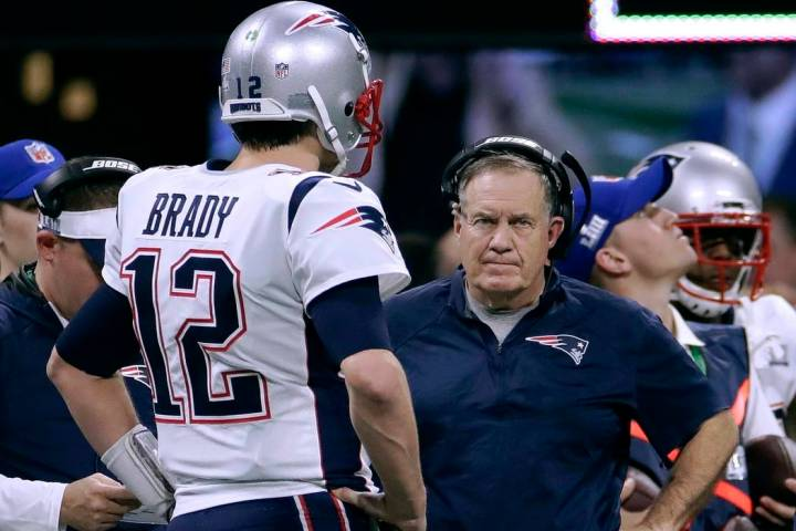 New England Patriots' Tom Brady, left, talks with head coach Bill Belichick during the first ha ...