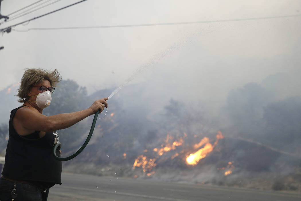 Patricia Dennison uses a hose to try to stop an advancing wildfire from affecting her business, ...
