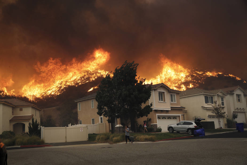A wildfire approaches a residential subdivision Thursday, Oct. 24, 2019, in Santa Clarita, Cali ...