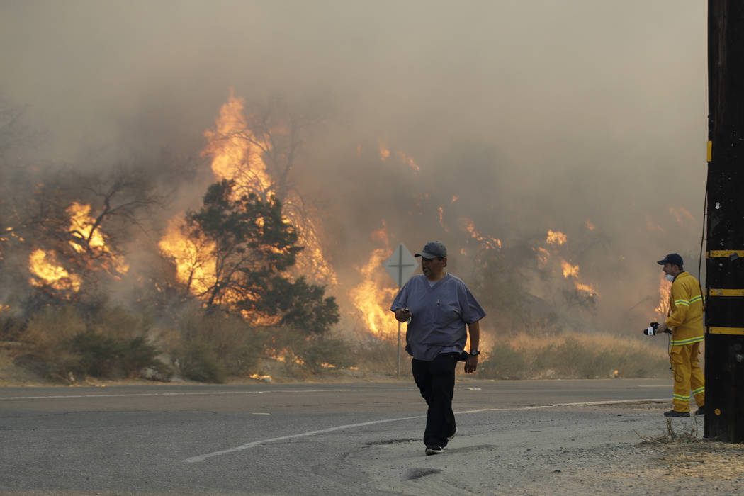 A man walks along Sierra Highway as flames from a wildfire overtake a hillside Thursday, Oct. 2 ...