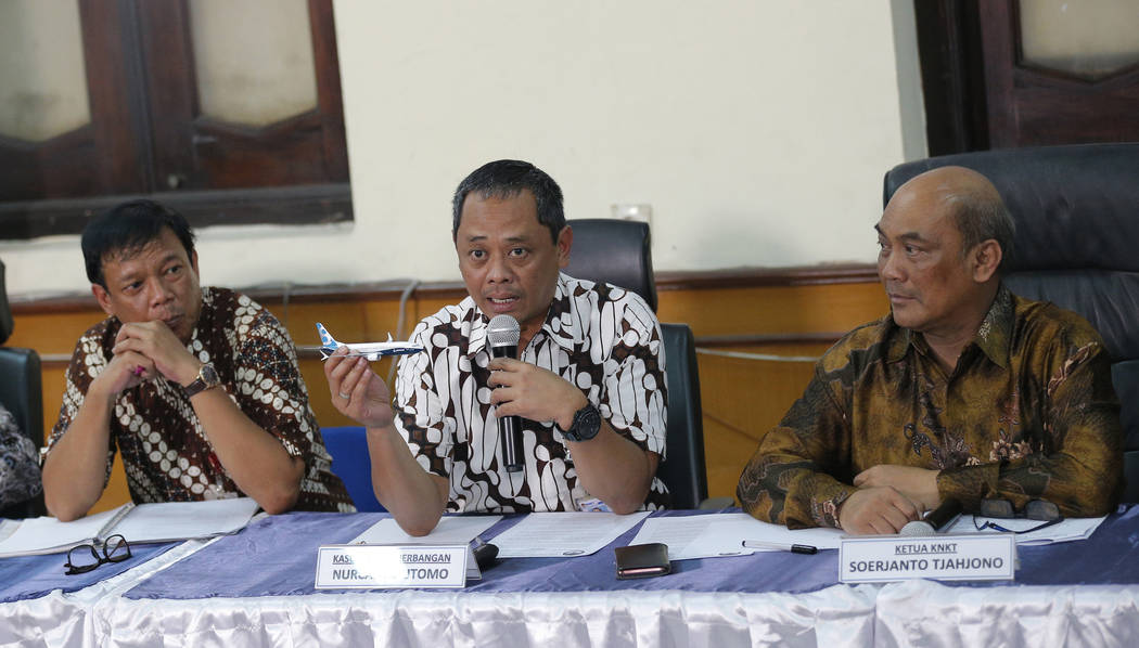 National Transportation Safety Committee investigator Nurcahyo Utomo, center, holds a model of ...
