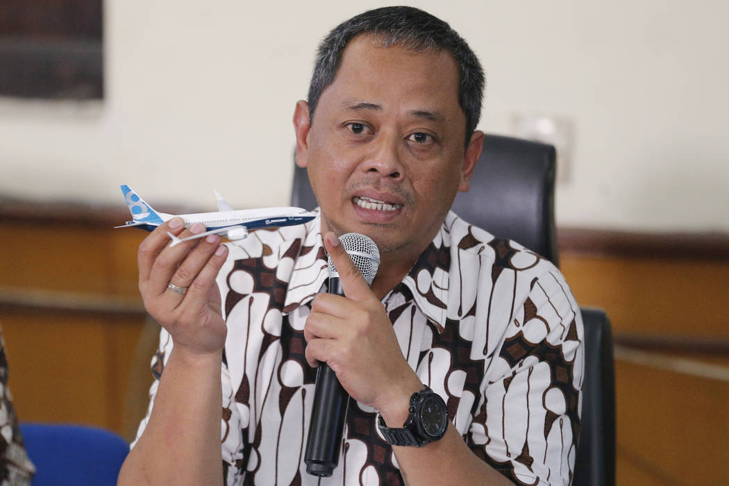 National Transportation Safety Committee investigator Nurcahyo Utomo holds a model of an airpla ...