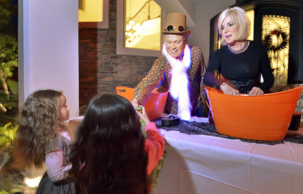 Bruce Burnett and his wife, Kris, pass out candy at their home on Halloween night at the Red Ro ...