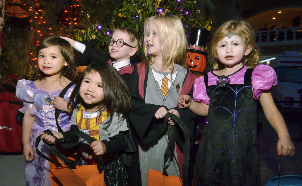 Trick-or-treaters, from left, Sophia and Stella Slade, Colton Sugars, Savannah Rourke and Addis ...