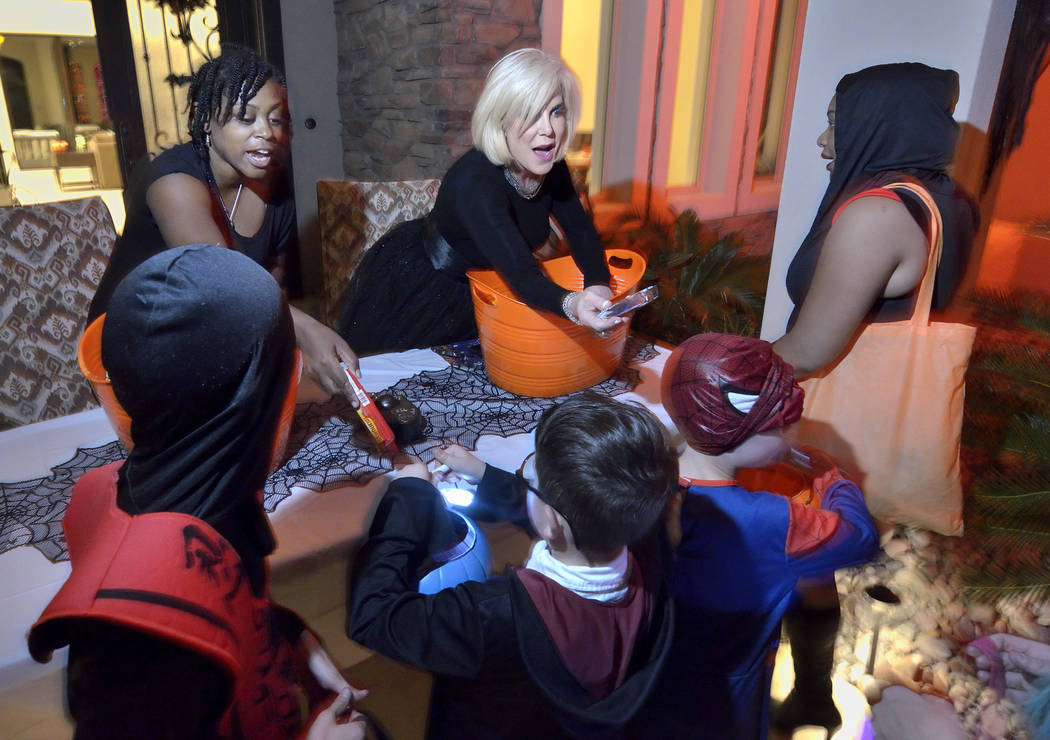 Tiffany Flowers-Holmes, left, and Kris Madsen Burnett hand out candy on Halloween night. (Bill ...