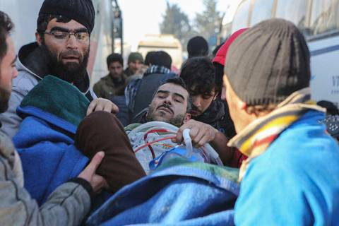 An injured Syrian arrives at a refugee camp in Rashidin, near Idlib, Syria, after was evacuated ...