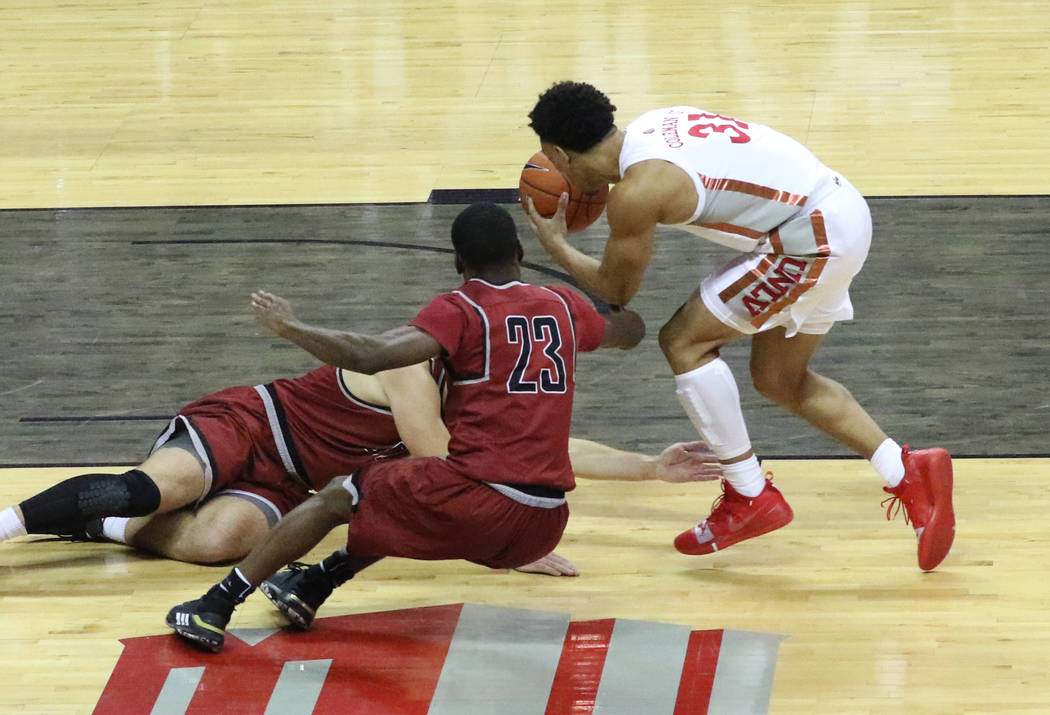 UNLV's guard Marvin Coleman (31) fights for a loose ball against West Coast Baptist guard Josep ...
