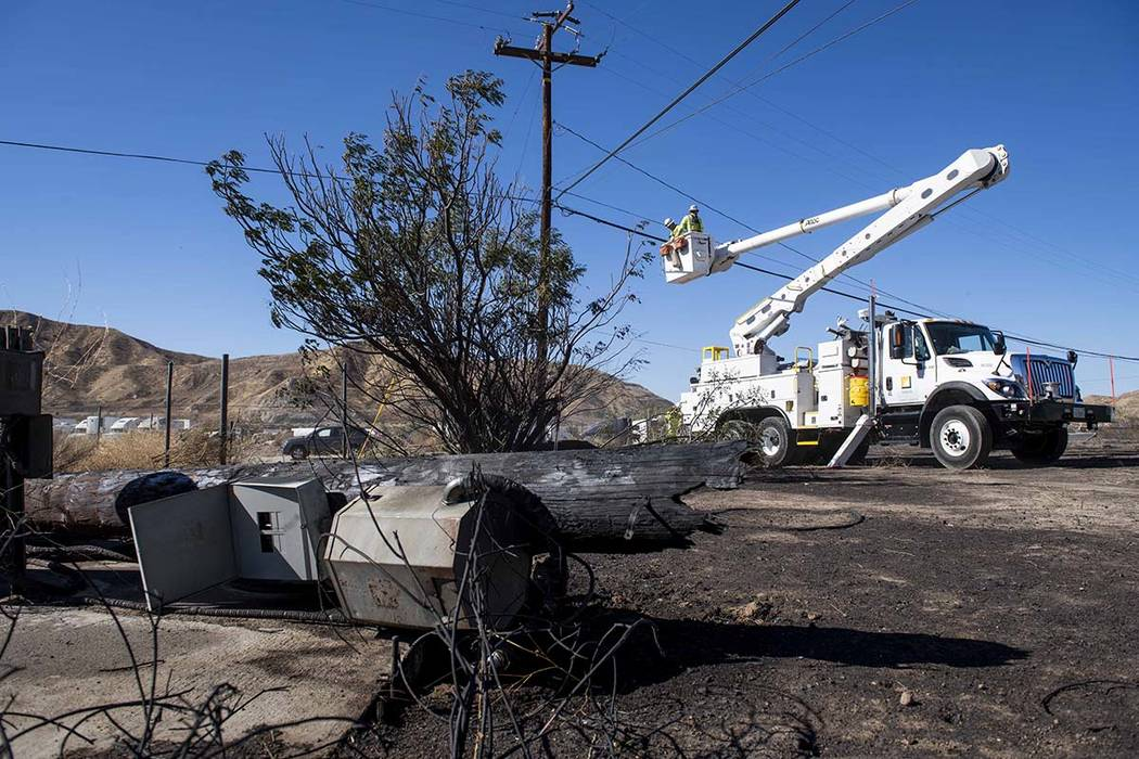 SoCal Edison workers replace power lines that were damaged from the Tick Fire, Thursday, Oct. 2 ...
