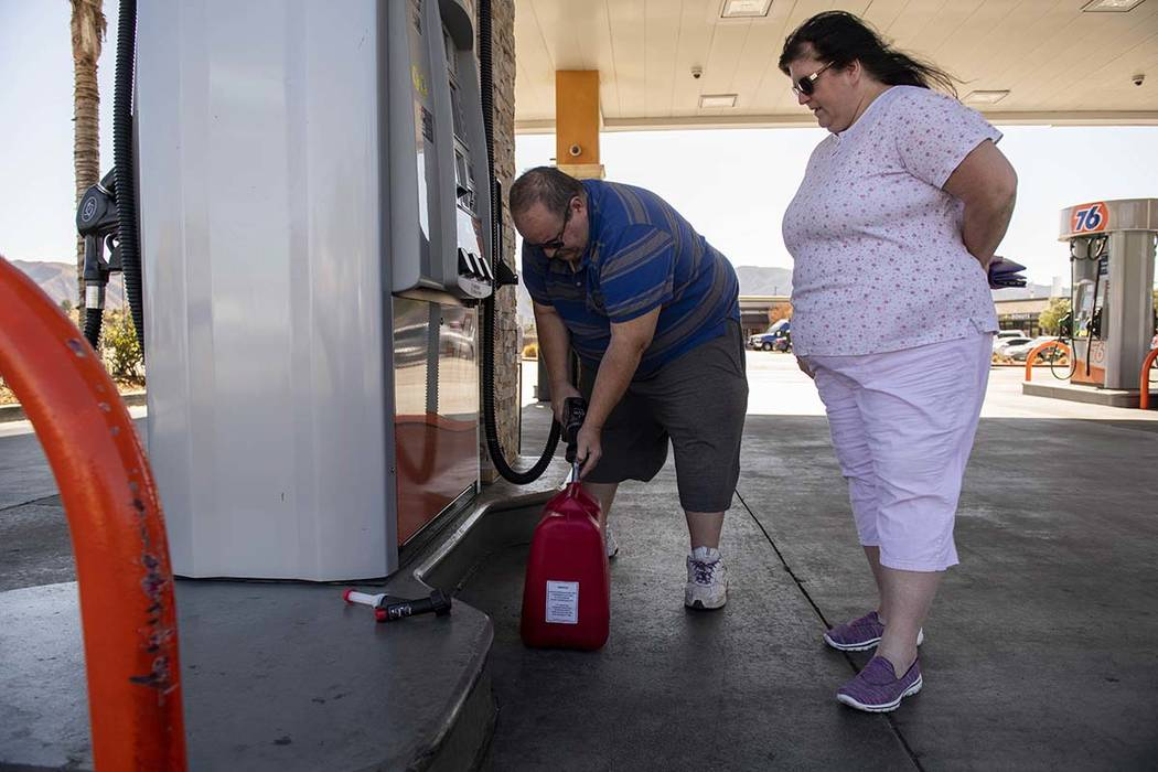 Richard and Sheri Rose fill a plastic jerry can to power their generator while the power remain ...