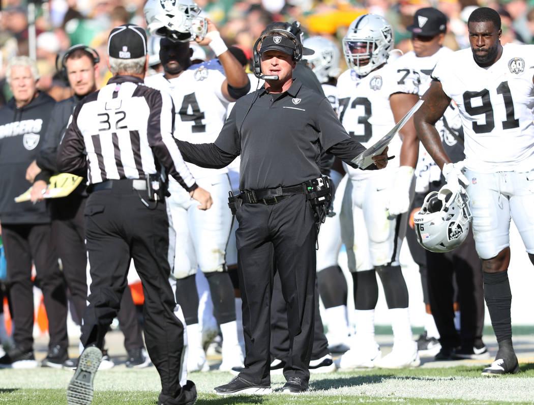 Oakland Raiders head coach Jon Gruden gestures to line judge Jeff Bergman (32) as his challenge ...