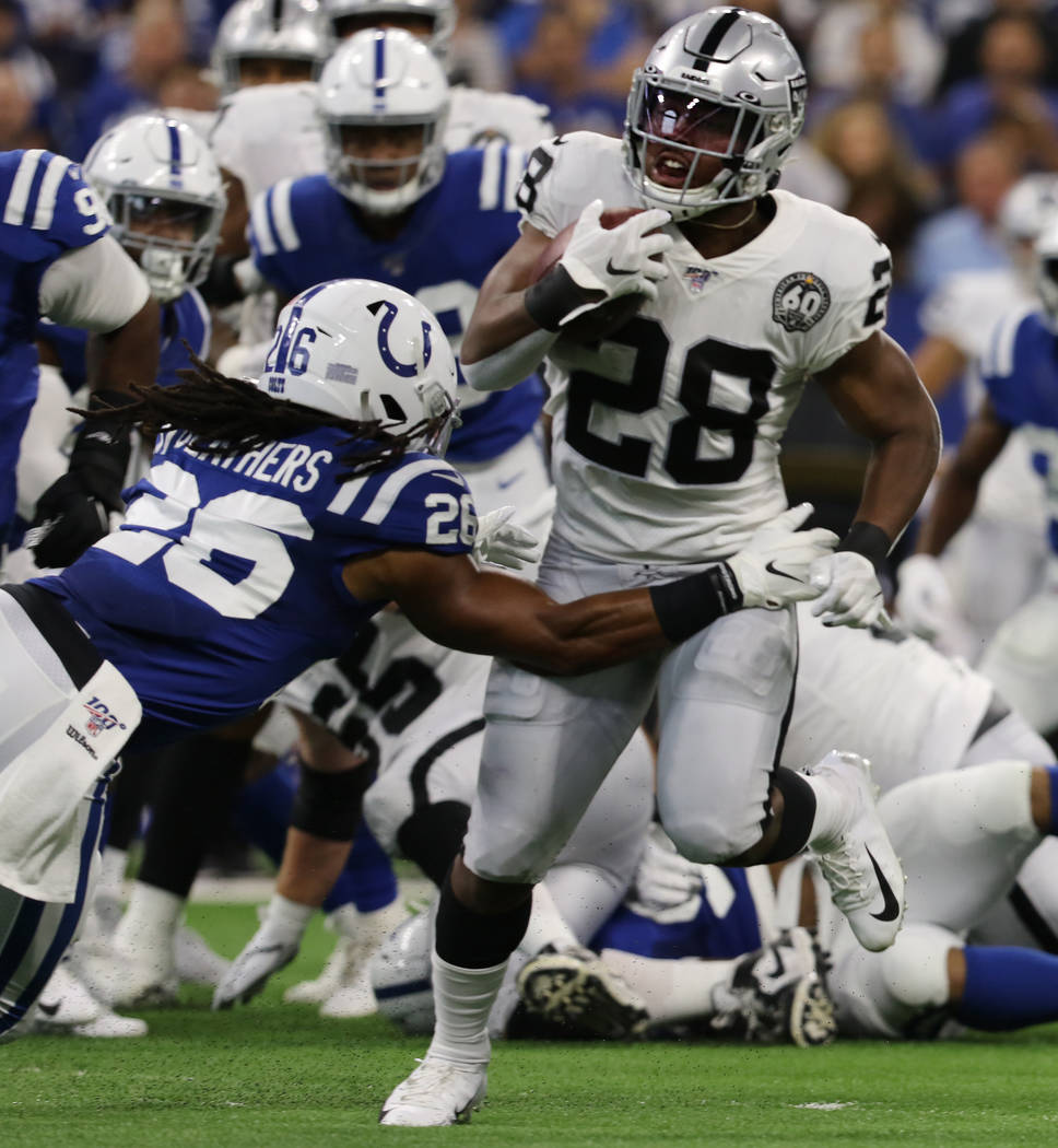 Oakland Raiders running back Josh Jacobs (28) runs -past Indianapolis Colts strong safety Clayt ...