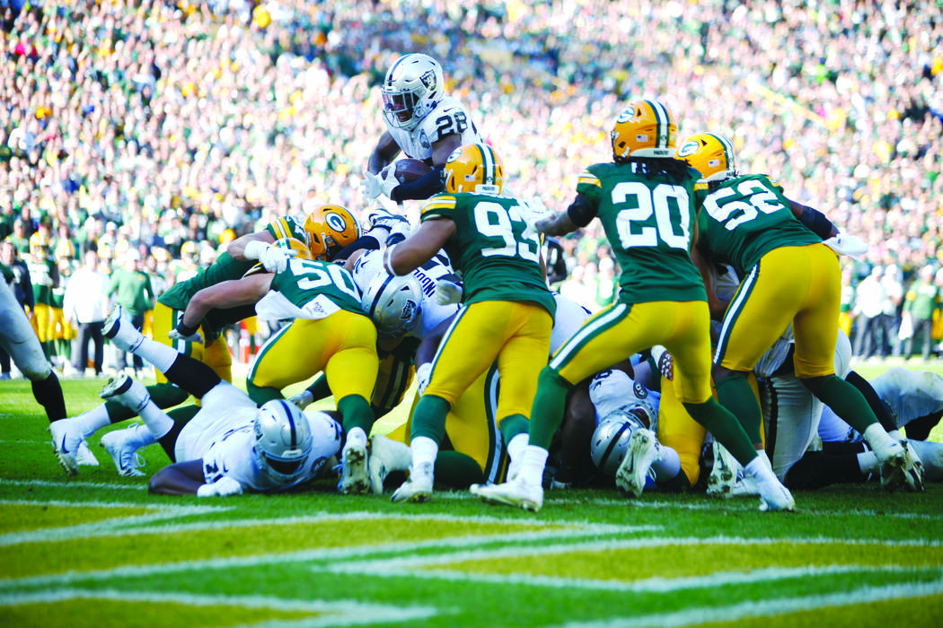 Oakland Raiders running back Josh Jacobs (28) tries to jump over Green Bay Packers' defenders t ...