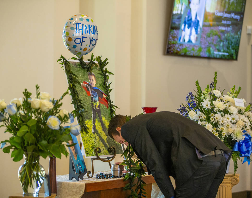 Sean Murray, center, weeps and touches the urn of his son Gavin Murray, 6, during Gavin's fune ...