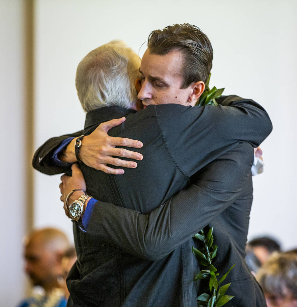 Sean Murray, right, is hugged by his father, Gordon Murray, during a funeral service for his s ...