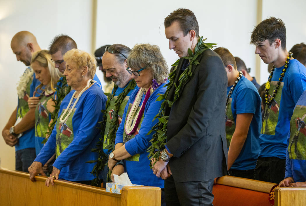Sean Murray, center, prays next to grandparents Kathleen and Chuck Wheeler and many others duri ...
