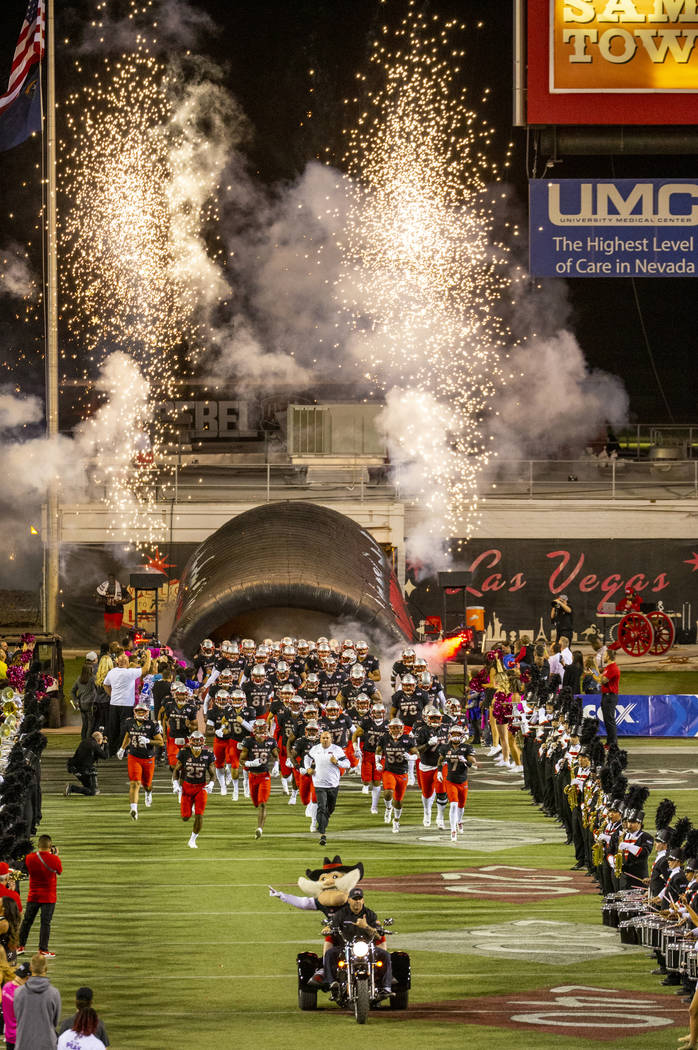 UNLV players and coaches take the field versus San Diego State for their football game at Sam B ...