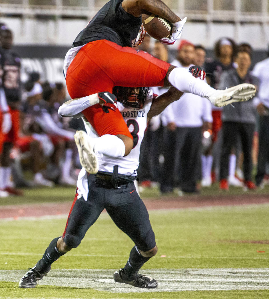 UNLV Rebels tight end Noah Bean (11, above) attempts to go over San Diego State Aztecs cornerba ...