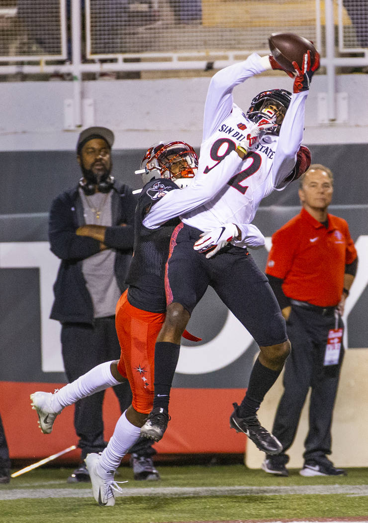 UNLV Rebels defensive back Myles Plummer (14) attempts to break up a pass to San Diego State Az ...