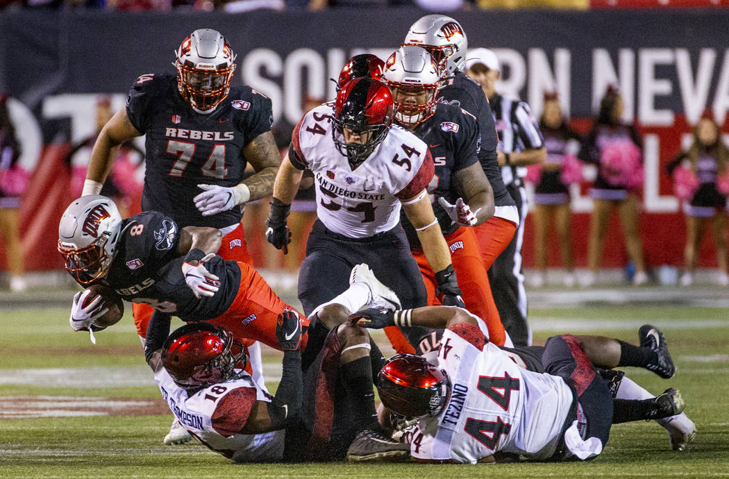 UNLV Rebels running back Charles Williams (8) dives over San Diego State Aztecs safety Trenton ...