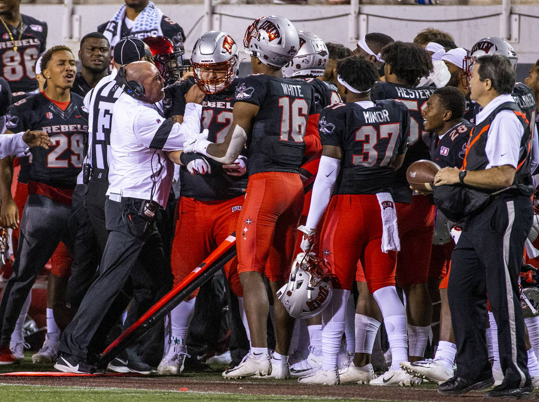 UNLV Rebels head coach Tony Sanchez attempts to control his offensive lineman Matt Brayton (72) ...