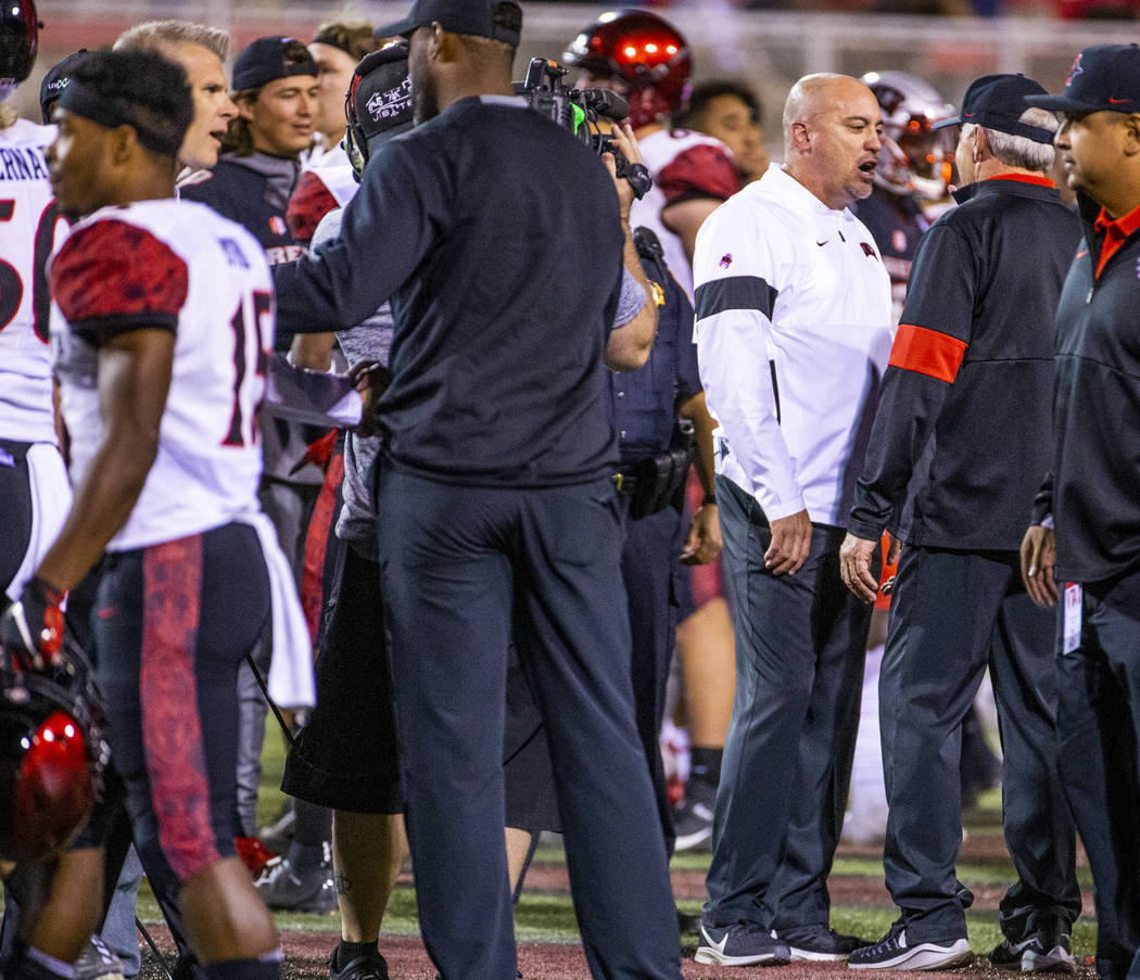 UNLV Rebels head coach Tony Sanchez chats with San Diego State Aztecs head coach Rocky Long at ...
