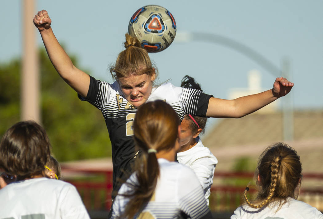 Faith Lutheran's Amelia McManus (20) heads the ball away from Arbor View defenders during the f ...