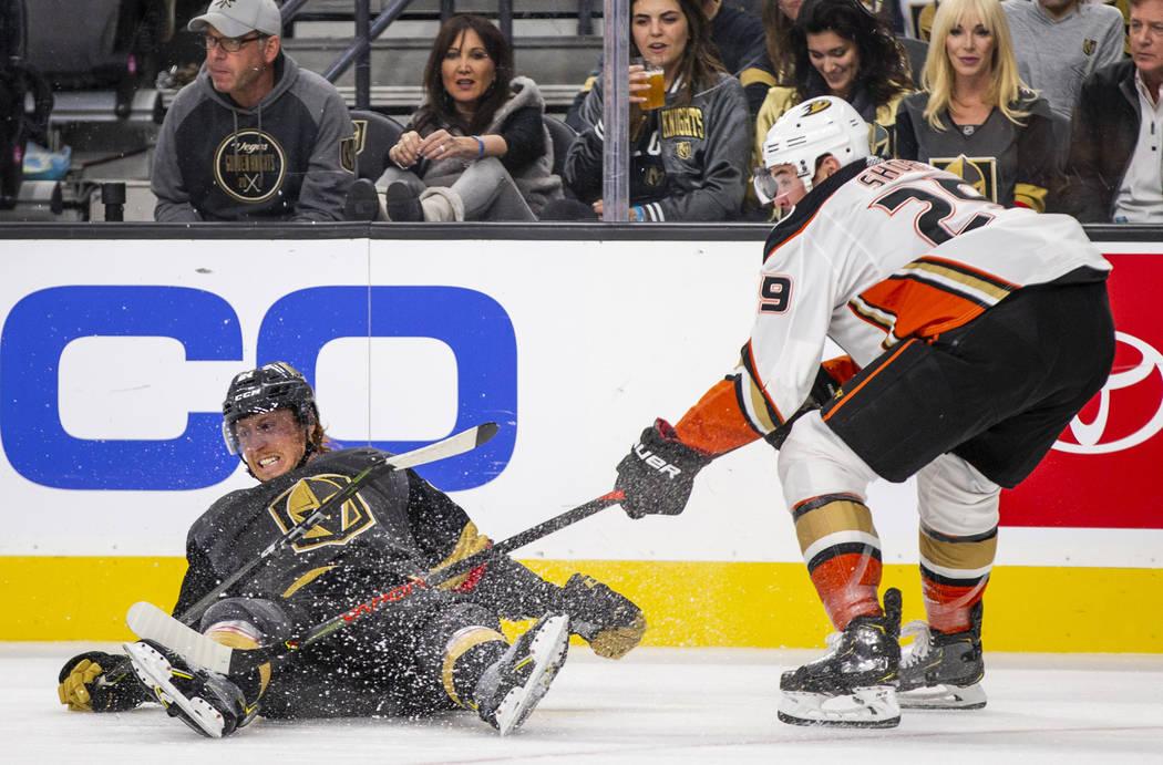 Vegas Golden Knights center Cody Eakin (21) is taken down to the ice by Anaheim Ducks center De ...